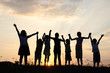 Silhouette, group of happy children playing on meadow