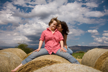 Sisters seated on a straw bale.