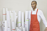 Portrait of printing press worker standing with paper rolls in background