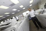 Man working in printing press between two cash register machine