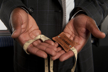 Close-up of hands holding measuring tape and tag