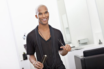 Smiling male hairdresser holding scissor and hairbrush