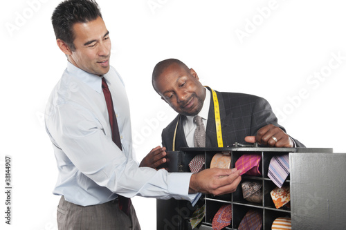 Man selecting neckties with tailor standing besides