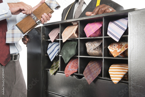 Cropped image of man holding tie press standing besides shelf
