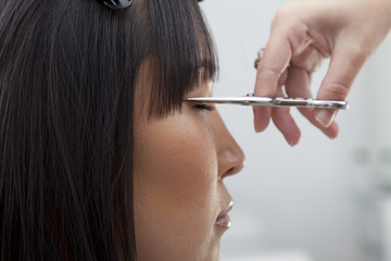 Close-up view of hairstylist cutting hair