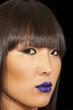 Close-up view of stylish Asian woman wearing blue lipstick