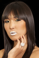 Woman posing on black background wearing beautiful ring with white lipstick