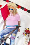Guitarist lying in bathtub