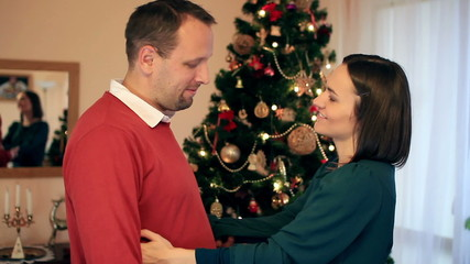 Couple talking in front of christmas tree