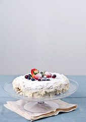 Homemade cake with fresh berries, icing sugar goes on top