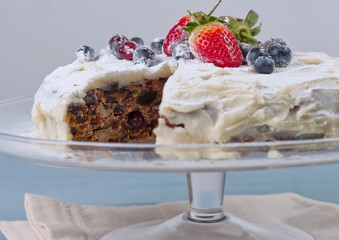 Homemade cake with fresh berries, one slice out