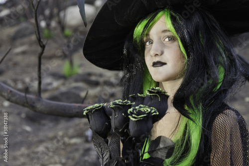 Little witch holding black roses looking away