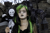 Portrait of girl dressed up as witch while her friends dressed up in skeleton costume
