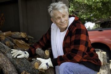 Senior man sitting besides firewood log