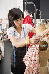 Female fashion designer pinning costume on mannequin