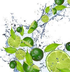 Limes falling in water splash, isolated on white background