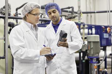 Two men working in bottling factory