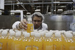 Quality control worker checking juice bottle on production line