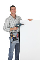 Handyman with a drill and blank board
