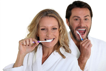 Couple in bathrobes cleaning teeth
