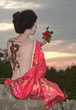 Geisha with dragon tattoo at sunset