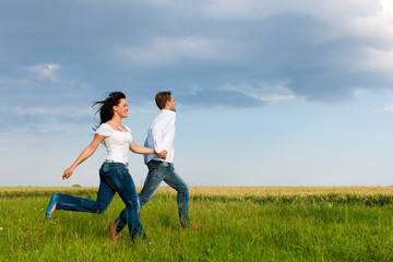 Happy couple running on a dirt road
