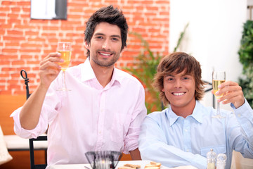 homosexual couple celebrating event at restaurant