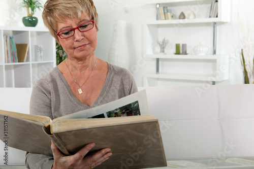 grandmother skimming through family album in lounge