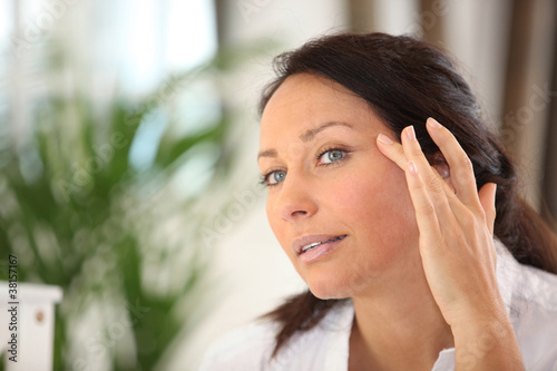 a woman spreading out cosmetic cream on her face