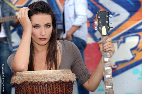 Musician leaning on a drum and holding a guitar