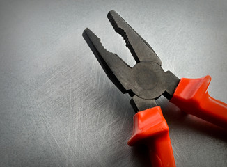 Pliers on the steel background