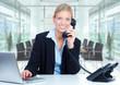 Geschäftsfrau mit Telefon und Notebook