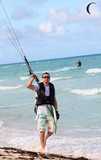 Man involved in kiteboarding on the coast of Cuba. poster