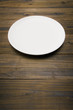 木のテーブルに白色の丸皿のアップ