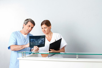 Zahnarzt und Zahnarzthelferin analysieren Röntgenbild