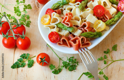 Delicious heart-shaped pasta with tomatoes and asparagus