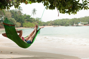View nice woman lounging in hammock in tropical environment