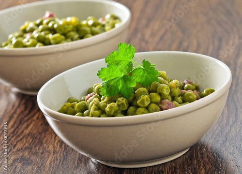 Peas with bacon in terracotta bowl.