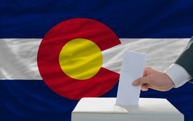 man voting on elections in front of flag US state flag of colora