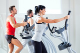 Fototapety man and woman with elliptical cross trainer at gym