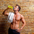 muscle shaped man at gym relaxed drinking