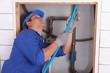 Plumber feeding blue flexible pipe behind a tiled wall