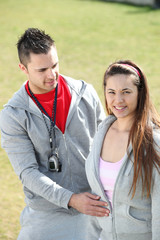 Sports trainer and young woman outdoors