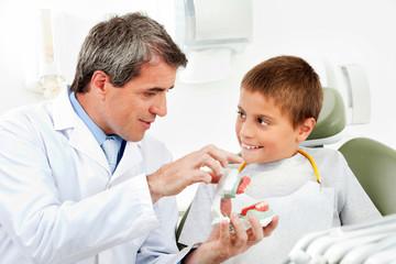 Zahnarzt erklärt Kind ein Gebiss