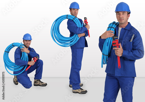 blue collar with hard hat carrying hose on his shoulder