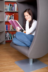 Young woman enjoying a good book in the library