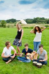 junge leute musizieren und tanzen im gras