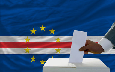 man voting on elections in front of national flag of capeverde