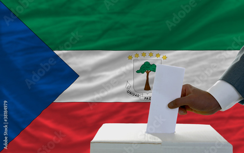 man voting on elections in front of national flag of equatorial