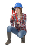 Woman holding bolt cutter whilst in crouching position